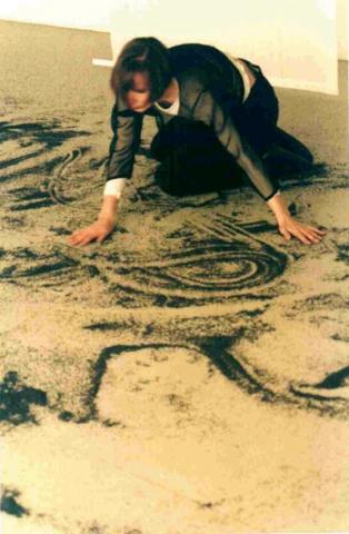 Spielräume – Interaktion der Künste | Das aus schwarzem Sand gestreute magische Quadrat wird im Rahmen der tänzerischen Interventionen aufgelöst